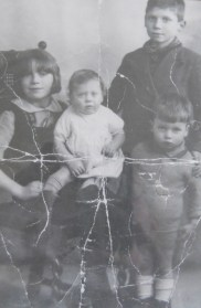in this pre war photograph, John is pictured front right, with his sister Rose as a baby. His brother Bill and sister Mabel are also in the photograph.